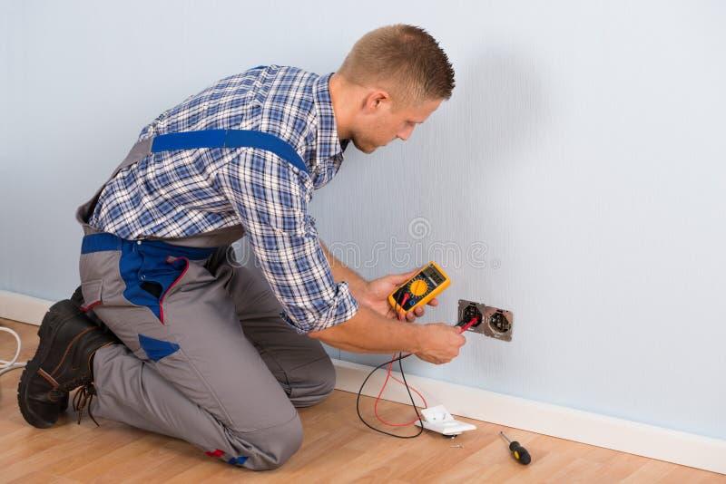 检查电压的电工与多用电表 库存图片