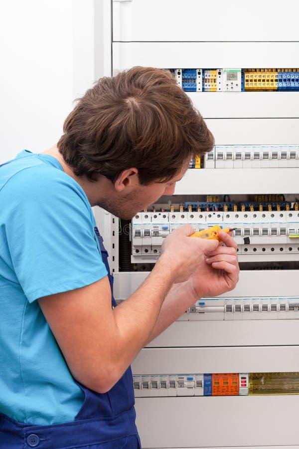 检查电压的年轻安装工 免版税图库摄影