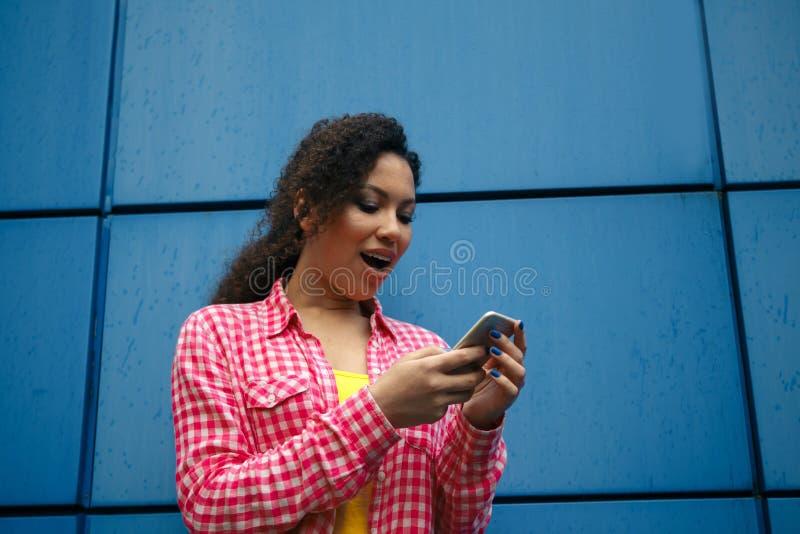 检查电子邮件箱子和读消息的情感年轻有吸引力的女性表达的惊奇与祝贺  库存图片