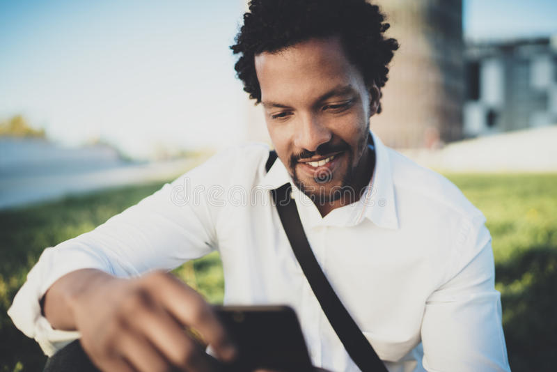 检查电子邮件的年轻有胡子的非洲人在智能手机,当坐在晴朗的城市公园时 愉快的商人的概念 免版税库存图片