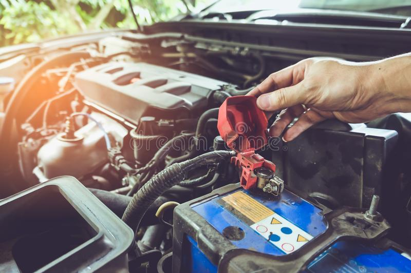 检查电池终端和引擎在的技术员的手 免版税库存照片