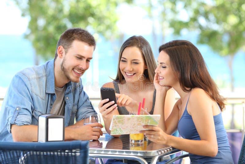 检查电话和地图的小组游人在度假 图库摄影