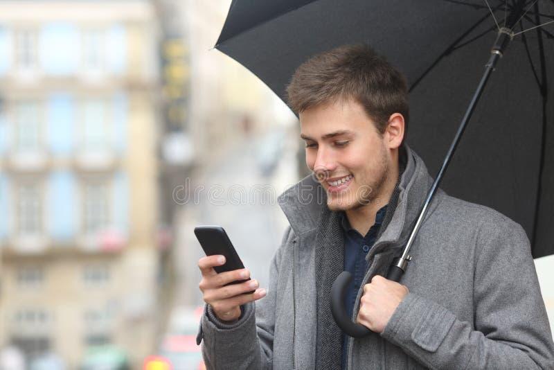 检查电话的愉快的人在一把伞下在冬天 免版税图库摄影
