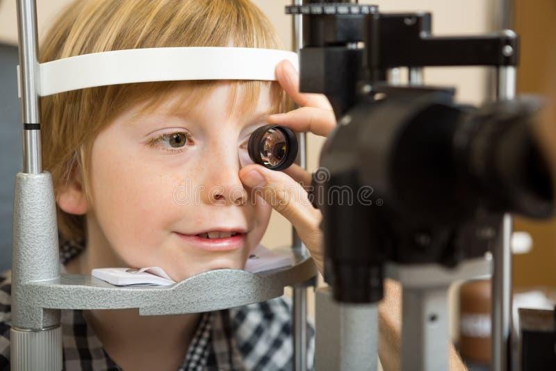 检查男孩的眼睛的眼镜师的手与透镜 库存图片