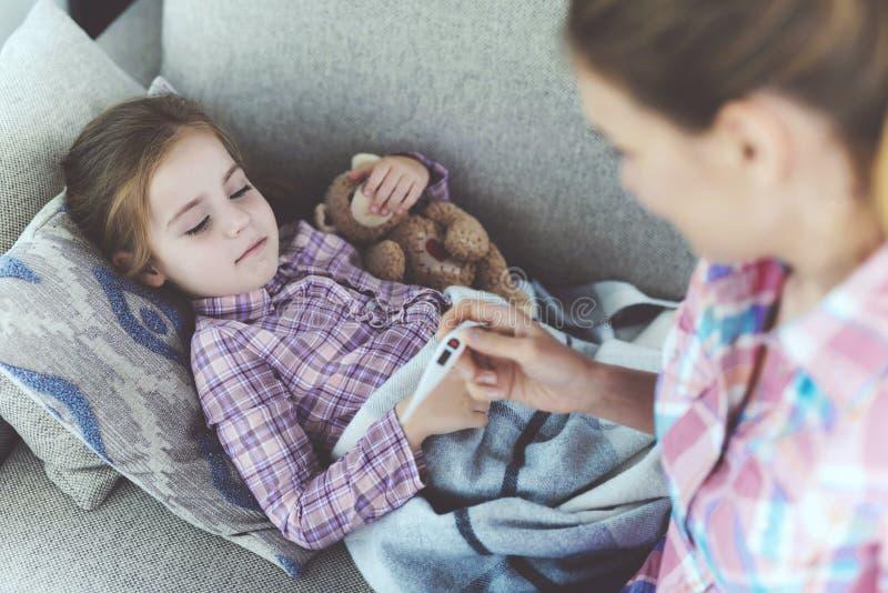 检查病态的儿童温度的仔细的母亲 图库摄影