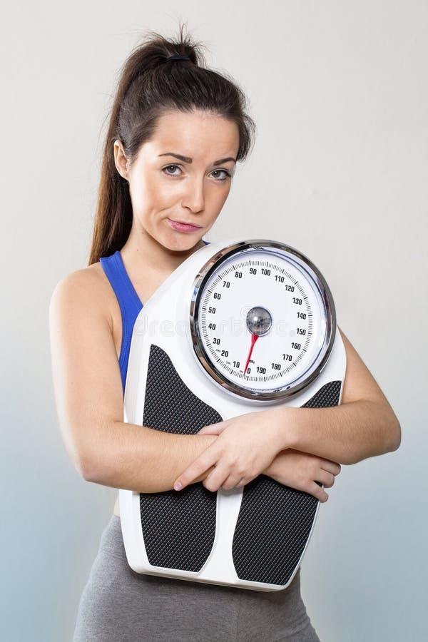 检查的减重半信半疑的20s健身房女孩藏品标度 库存照片