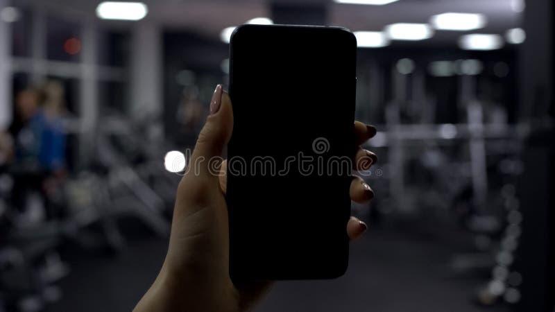检查相当数量在智能手机应用,黑屏幕的被烧的卡路里的妇女 图库摄影