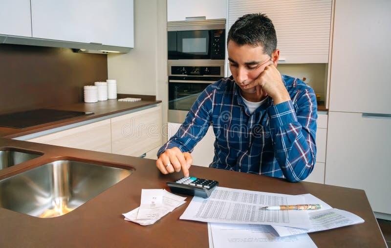 检查票据的年轻人 免版税库存照片