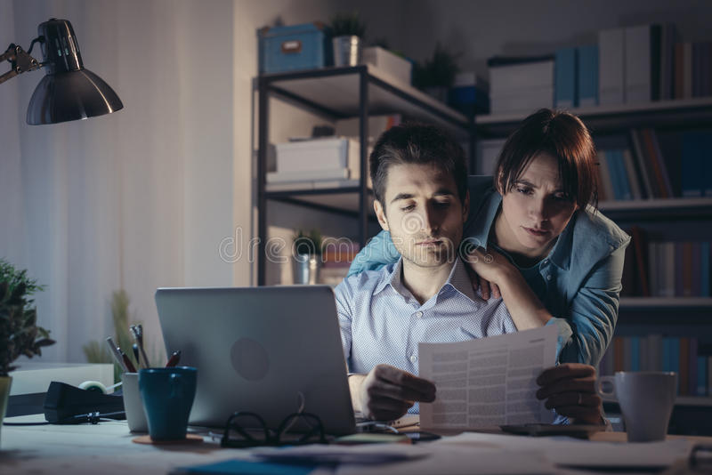 检查票据的年轻夫妇在晚上 库存图片