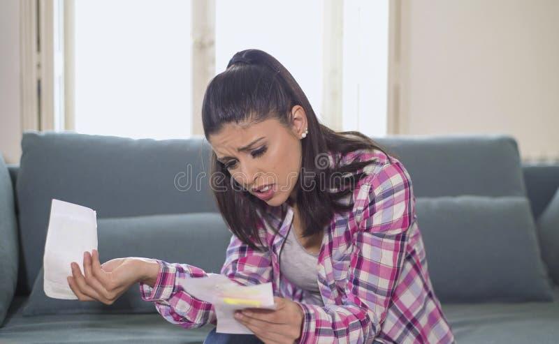 检查票据银行票据费用和月度付款在重音的年轻可爱和担心的西班牙妇女在公寓生活 免版税库存图片