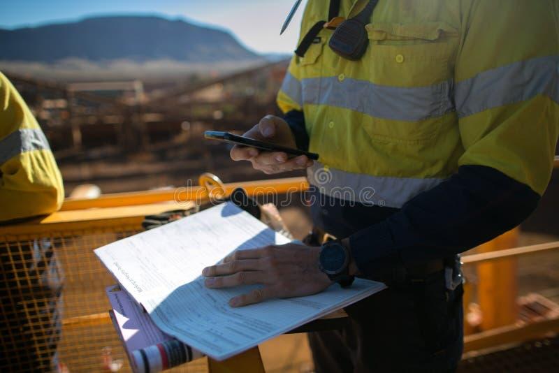 检查站点紧急电话号码的矿工监督员在有限空间许可证前叹气在进行高危险的工作之前 库存照片
