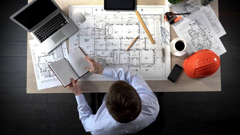 检查笔记的建筑师做在他的笔记本增加它到画大厦 免版税库存图片