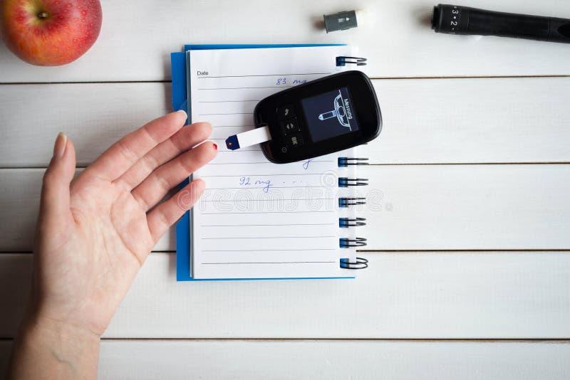 检查糖水平的妇女与glucometer 糖尿病测试医疗保健,糖尿病,医疗概念 免版税图库摄影