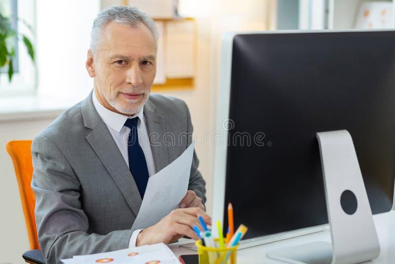 检查纸和计算机信息的悦目资深办公室工作者 库存照片