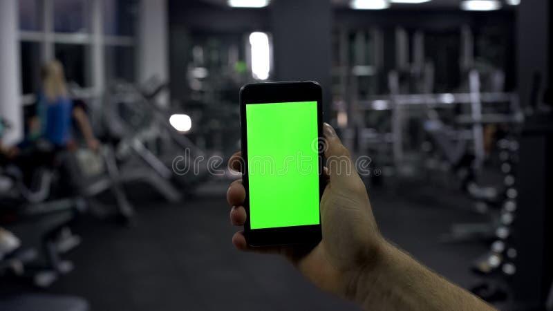 检查网上智能手机应用,监视脉冲,绿色屏幕的运动员 库存图片