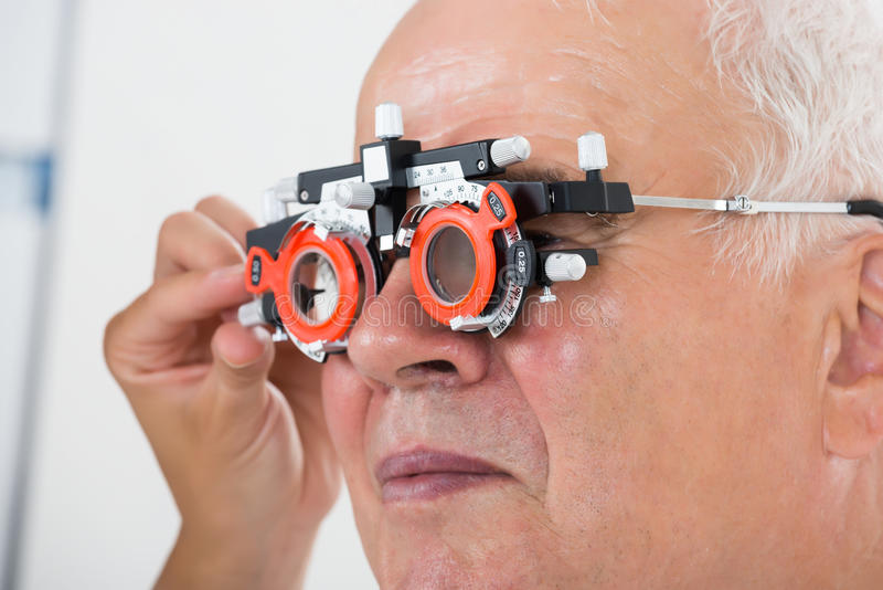 检查耐心视觉的验光师与试验框架 库存照片