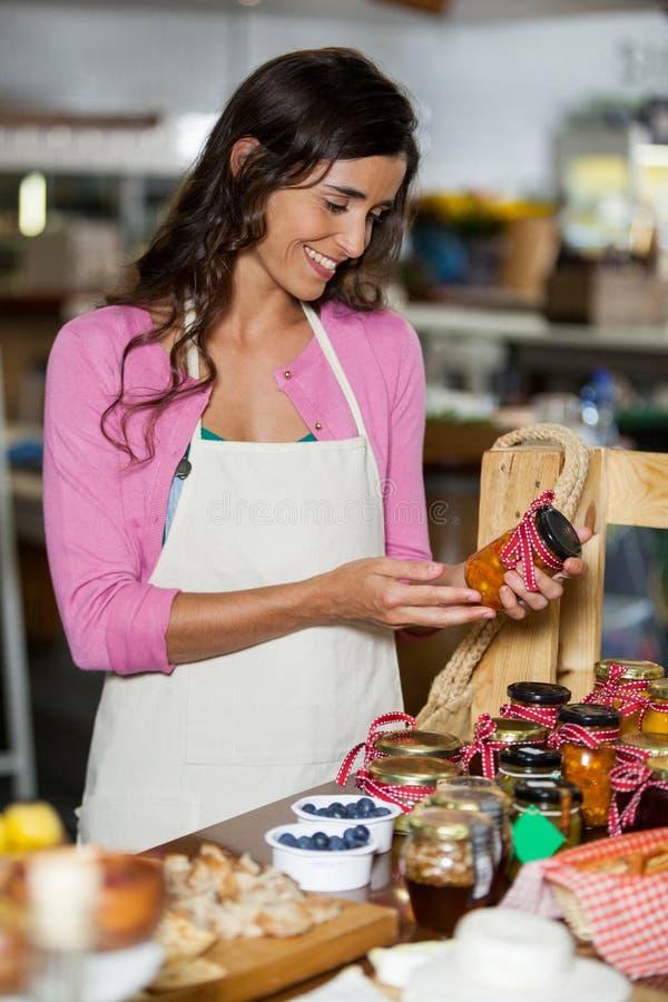 检查腌汁瓶子的微笑的职员在柜台 免版税库存图片