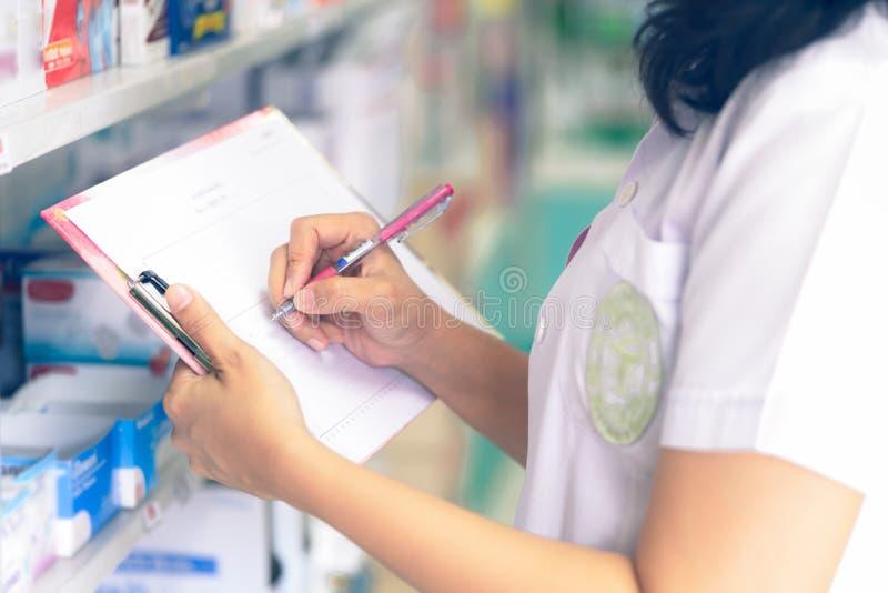 检查药物的分类的在药房的药剂师 免版税库存图片