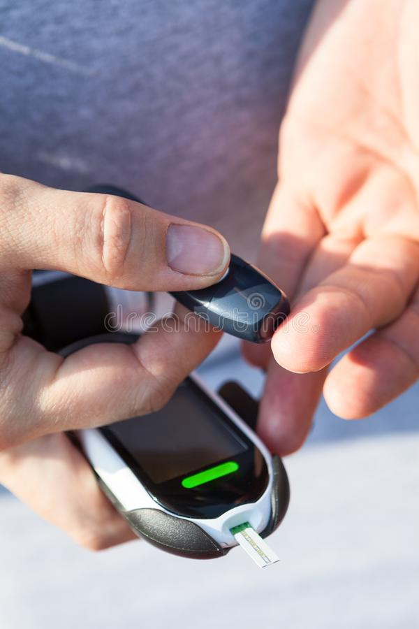 检查血糖水平的糖尿病 使用lancelet和glucometer,特写镜头视图的人 免版税库存照片
