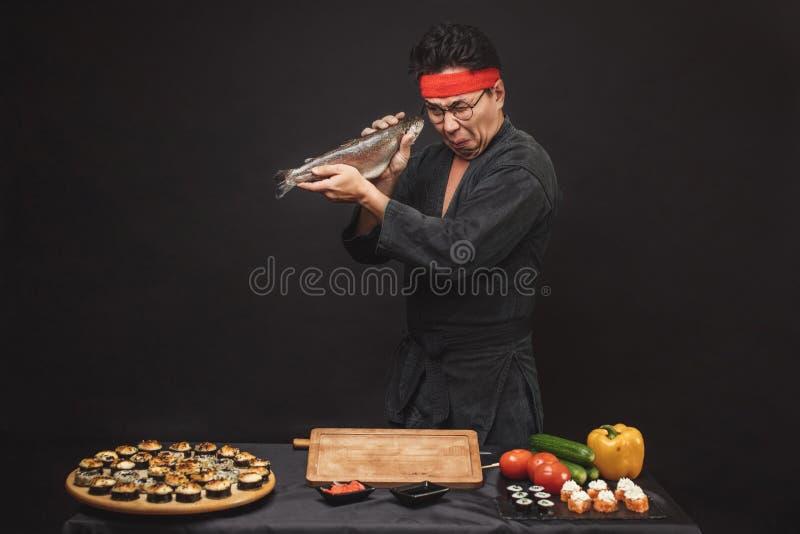 检查行鱼的滑稽的男性厨师烹调 图库摄影