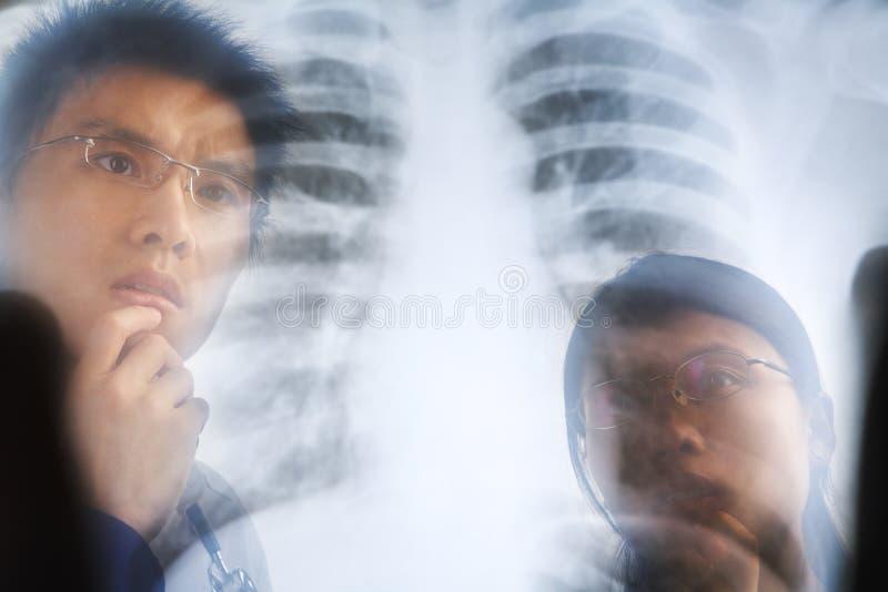 检查负X-射线的亚裔医生 图库摄影