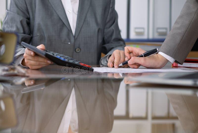 检查财政决算或计数由计算器收入的两名女性会计为报税表,手特写镜头 图库摄影