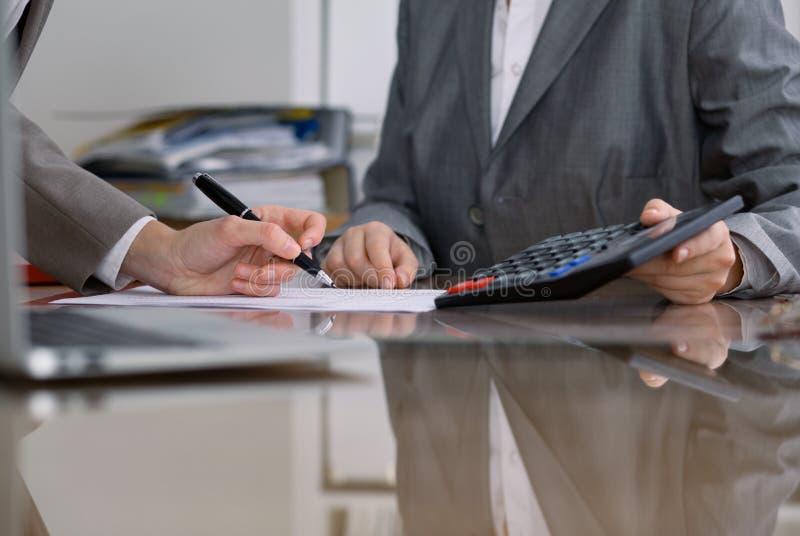 检查财政决算或计数由计算器收入的两名女性会计为报税表,手特写镜头 免版税库存照片