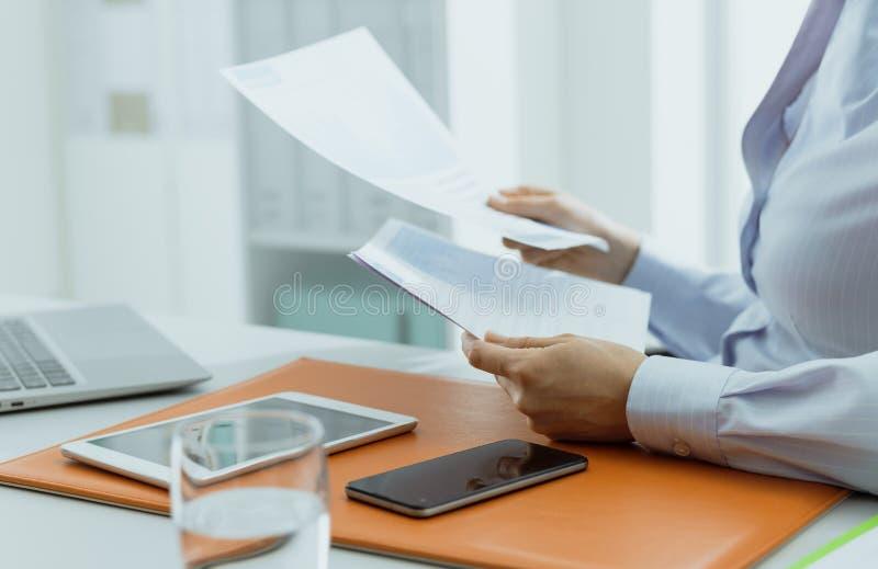 检查财政报告的商业主管在办公室 库存图片