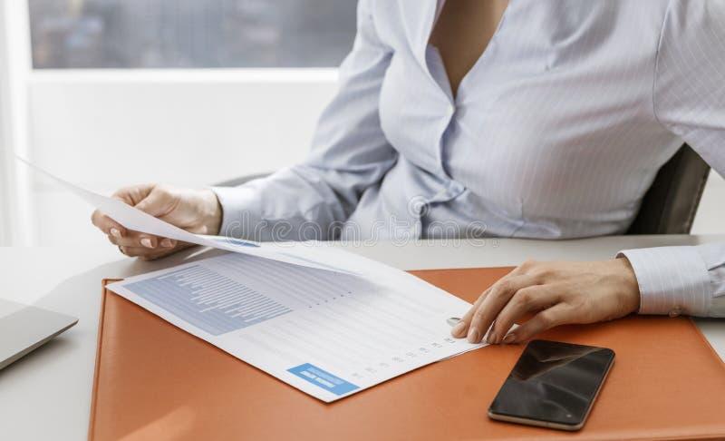检查财政报告的商业主管在办公室 免版税库存照片