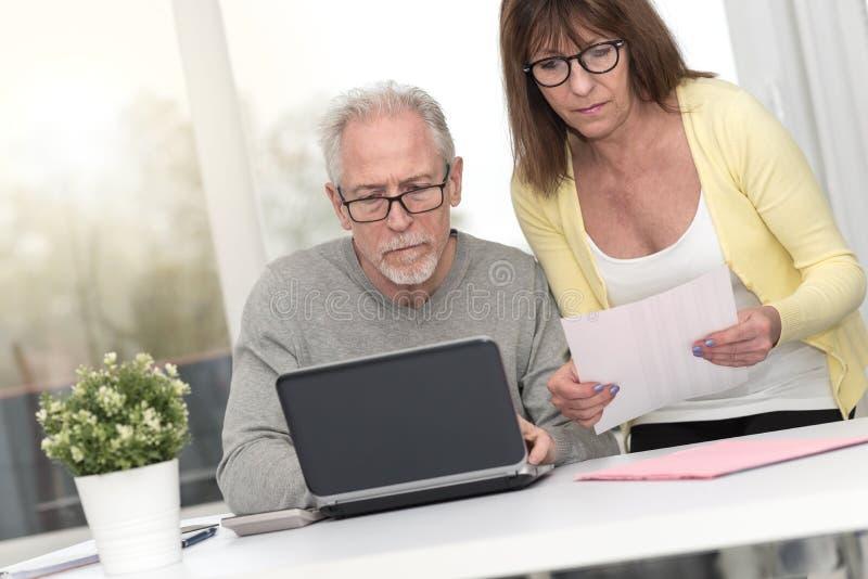 检查财政文件的资深夫妇 免版税库存照片