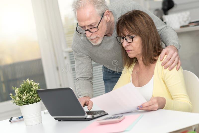 检查财政文件的资深夫妇 免版税库存图片