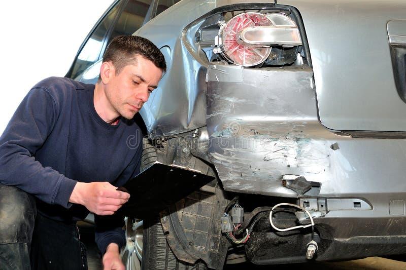 检查车身的技工在汽车修理店服务站 免版税库存照片