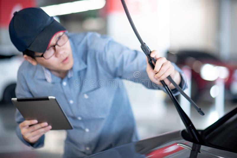 检查风档刮水器的亚裔汽车机械师 免版税库存图片