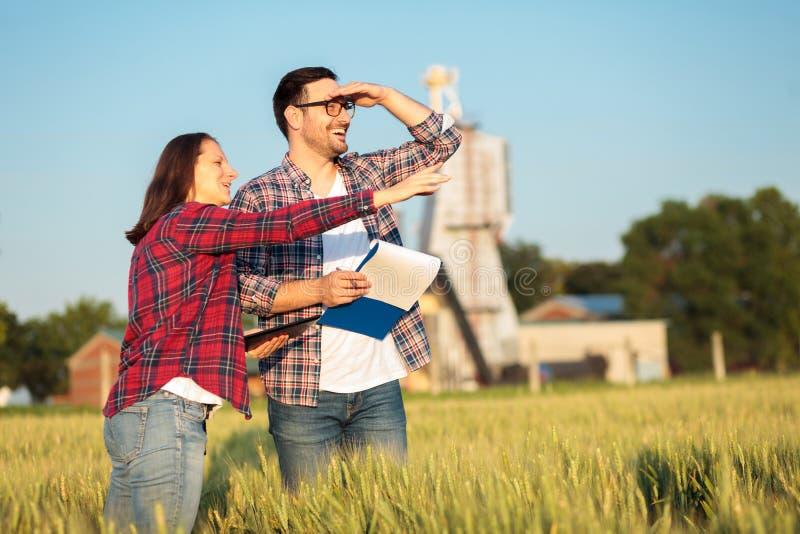 检查麦田的愉快的年轻女性和男性农艺师或农夫,在收获妇女指向某事在d前 免版税图库摄影