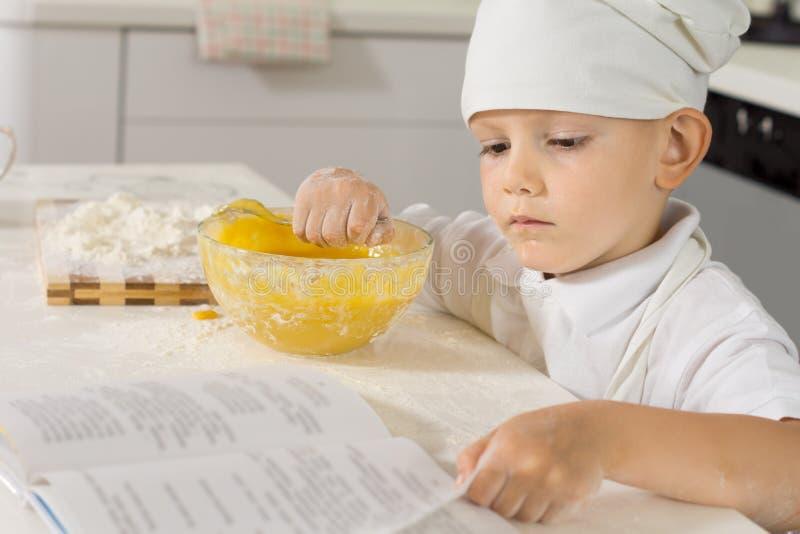 检查他的食谱的小男孩厨师,他烘烤 库存图片