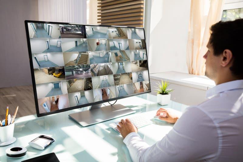 检查CCTV在计算机上的商人照相机英尺长度 免版税图库摄影
