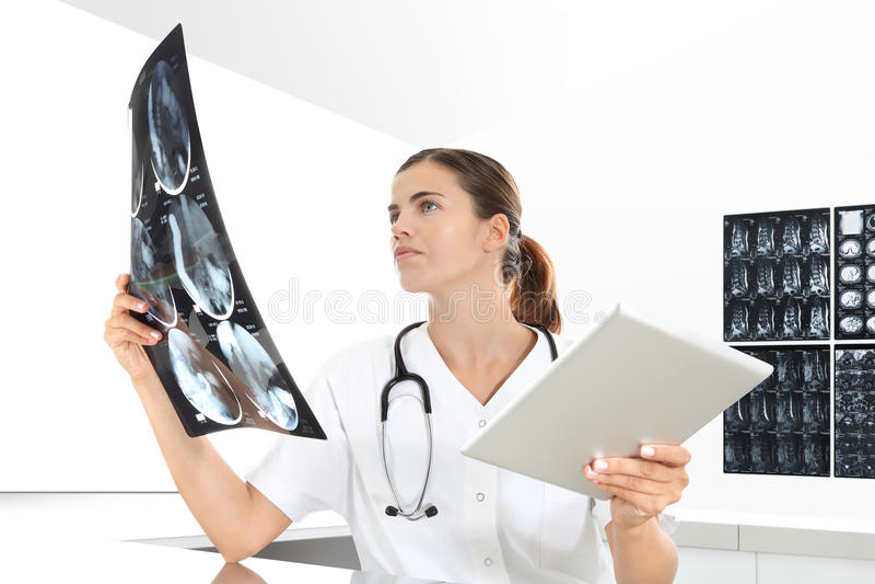 检查X-射线的放射学家妇女,与片剂,医疗保健 库存照片