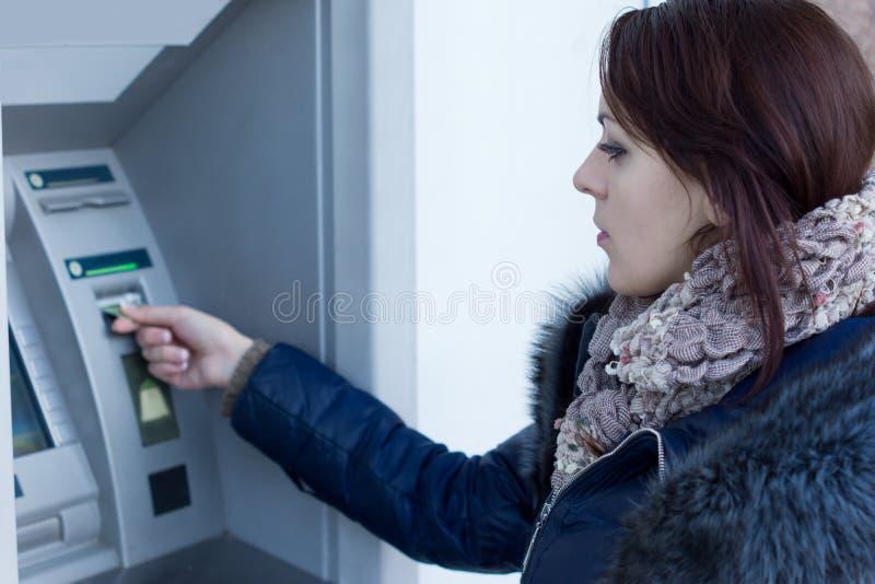 检索她的银行卡的妇女在ATM 免版税库存照片