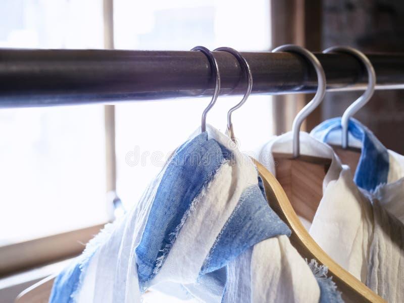 Download 棉布衬衣垂悬的显示在商店 库存照片. 图片 包括有 生活方式, 礼服, 挂衣架, 零售, 棉花, 精品店 - 62538554