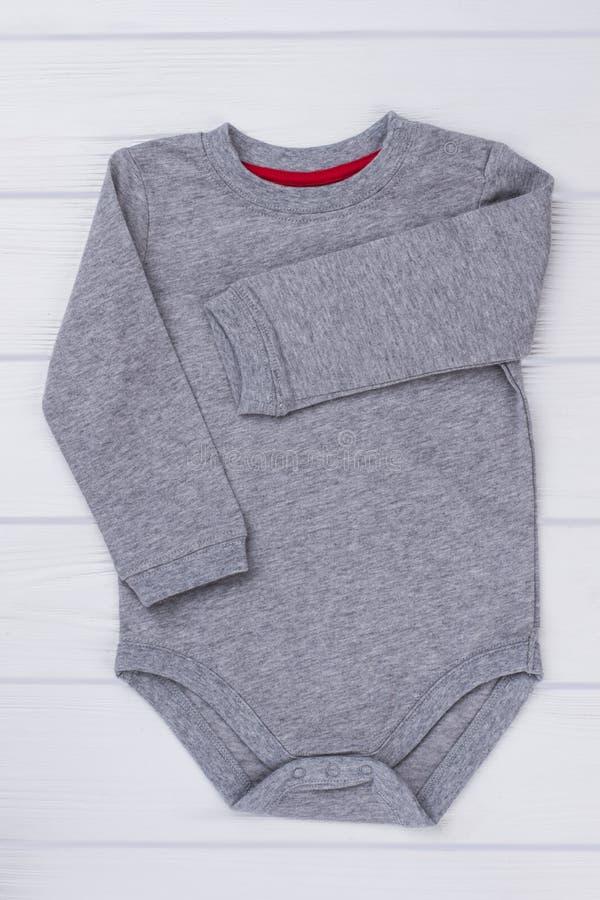 棉花在木头的婴孩onesie 免版税库存照片