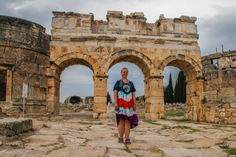棉花堡、代尼兹利、土耳其和一白年轻女人的一个经典古色古香的希腊剧院嬉皮礼服的 免版税库存照片