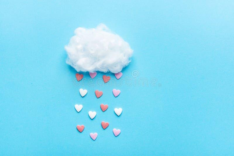 棉花球云彩雨冰糖洒在蓝天背景的心脏红色桃红色白色 补花艺术构成华伦泰 免版税库存图片