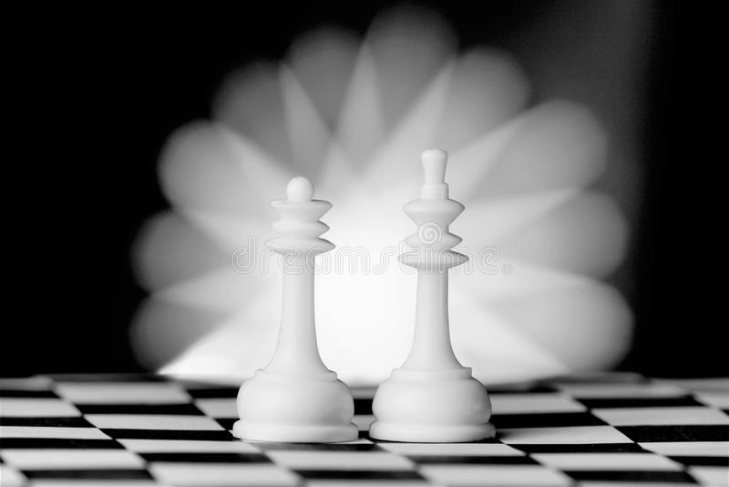 棋子国王和女王/王后,在委员会的 棋是与特别黑白的一场普遍的古老委员会逻辑对抗性比赛 库存图片