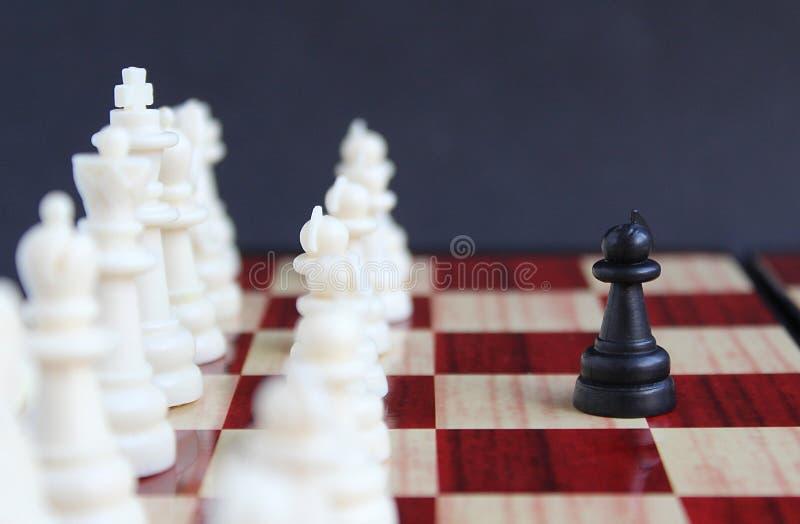 棋子黑色在一个整个小组的典当身分白色棋子前面 图库摄影