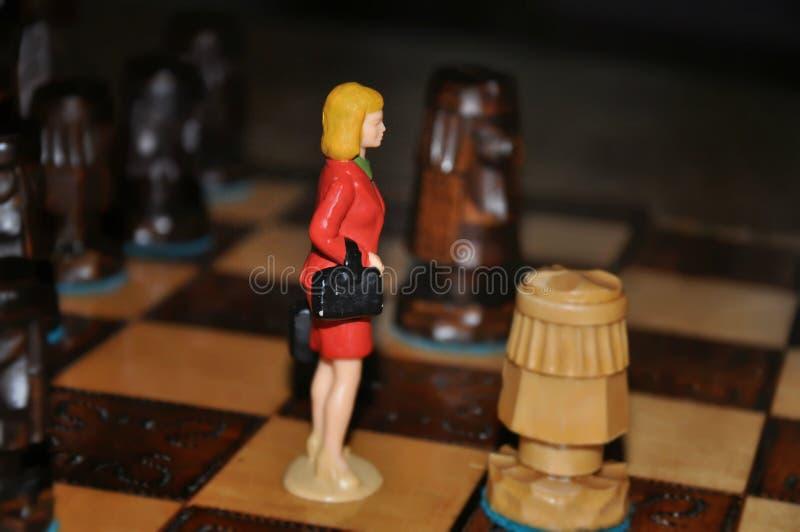 棋枰的微型妇女在木棋子之间 免版税库存照片