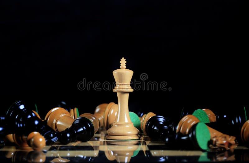 棋盘的白国王Standing在下落中 免版税库存照片