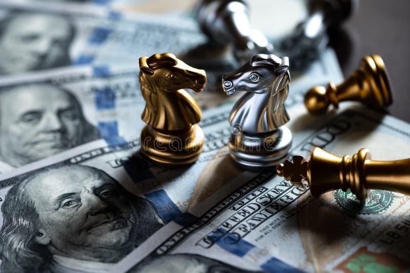 棋骑士在美元钞票站立互相反对 企业竞争和战略概念 免版税库存图片
