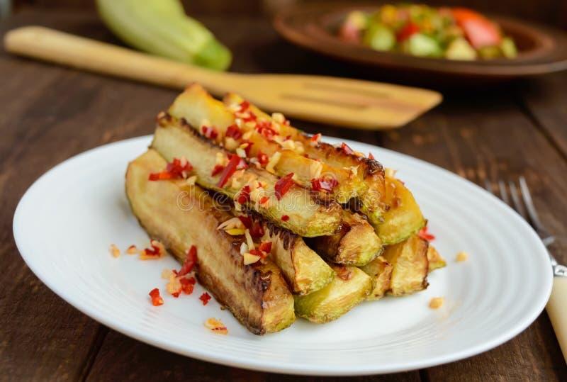 以棍子的形式辣被烘烤的夏南瓜南瓜用大蒜和辣椒 免版税库存照片