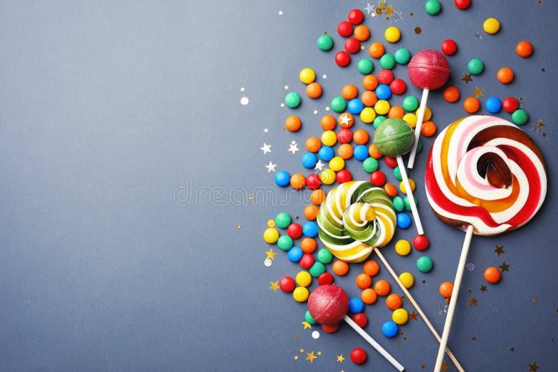 棒棒糖和五颜六色的糖果在灰色背景,顶视图 免版税库存图片