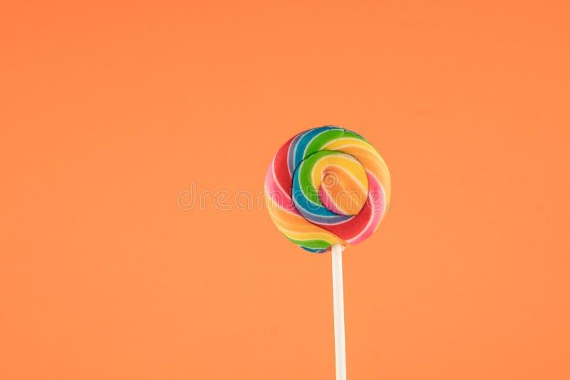 棒棒糖,大圆的彩虹在橙色背景隔绝的色的棒棒糖, 免版税库存图片